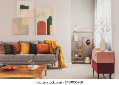 Yellow, orange, black and brown pillows on comfortable grey scandinavian sofa in bright living room interior with abstract paintings on the wall