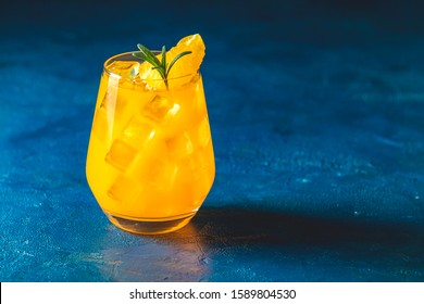 Yellow orange cocktail with tangerine and rosemary with ice in glass on dark blue concrete background , close up. Christmas and New Year holiday welcome drink