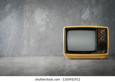 Yellow Orange color old vintage retro Television on cement table with  background .