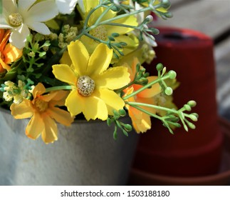 Yellow and orange fake flowers and red pot
