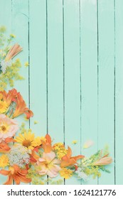yellow and orange flowers on green wooden background