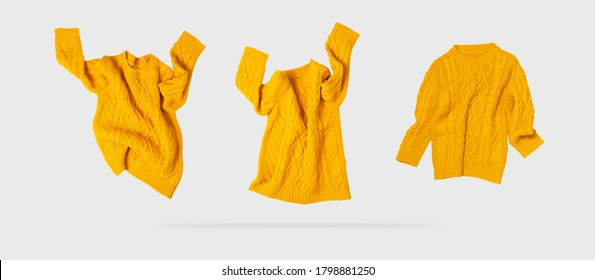Yellow orange flying women's autumn knitted sweater on light gray background. Creative clothing concept, trendy fall winter cozy sweater pullover jersey. Women's fashion, autumn discounts. Shopping