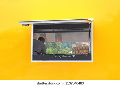 """yellow and orange food truck with a window and the text """"we love streetfood"""", rear view"""