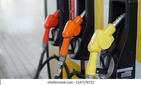 Yellow and Orange Fuel nozzle for  Pumping Gasoline and Diesel fuel at Gas station. Petrol station with Fuel oil dispenser.Selective focus