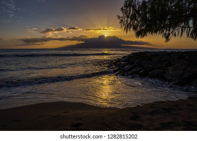 The yellow and orange light reflecting off the Maui surf while the sun sets behind the clouds gathering over the island of Lanai, Hawaii.