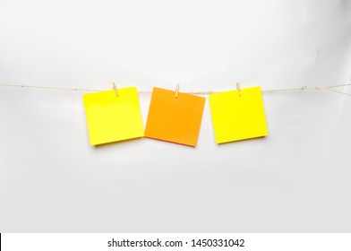 Yellow and orange paper hung in a rope with wooden clothespins