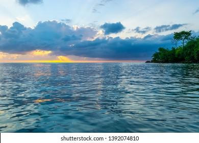 Yellow, orange, pink, blue skies illuminated as sunrays burst through the clouds at sunset. Breathtaking evening scenery on coast of tropical Caribbean island.