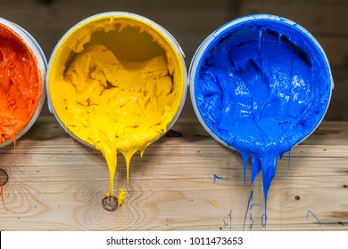 yellow orange and red colors of plastisol ink flowed out of the barrel. plastisol ink is specially for print on tee shirts and any fabric. the ink useful in tee shirt factory garment and industry