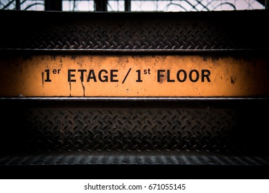 "Yellow and orange Stairs sign ""1st Etage / 1st floor"" with dark industrial metal stairs surrounding and a glimpse to the next level in the eiffel tower in paris on the last step to the first etage"