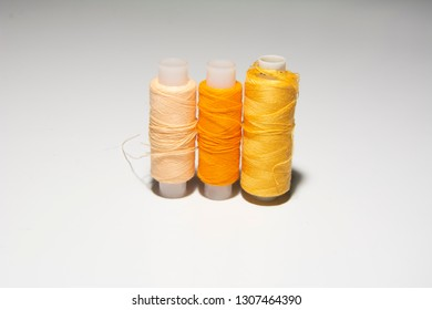 Yellow, orange thread for sewing on a white background.