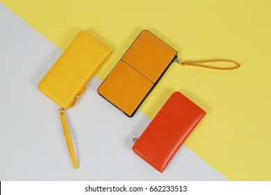 The Yellow and orange tone leather wallet isolated over white and yellow background.Concept  fashion Modern Pop Art.
