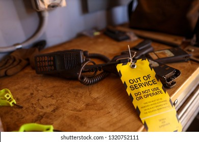 Yellow out of service tag attached on defect broken two way radio on the table do not use or operation construction mine site Perth, Australia