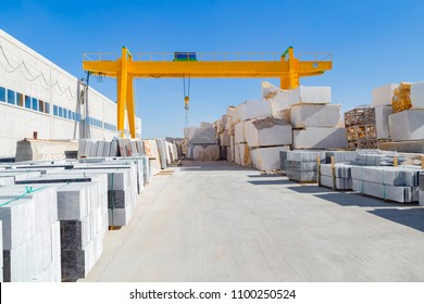 Yellow outdoor crane for marble factory, electric overhead traveling crane above the open warehouse and loading area in Afyonkarahisar.