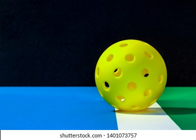 Yellow outdoor Pickleball on the boundry line of pickleball court with blue play area and green out of play area...with a black background.