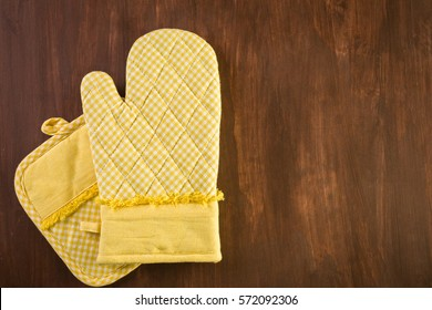 Yellow oven mitt on wood background.