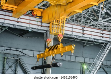 Yellow overhead crane carries cargo in engineering plant shop. Jib crab trolley with hooks and linear traverse.
