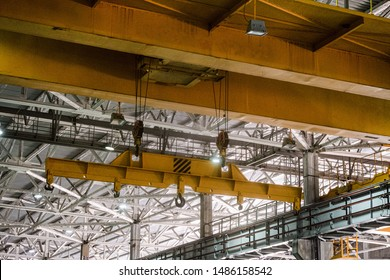 Yellow overhead crane. Jib crab trolley with hooks and linear traverse.