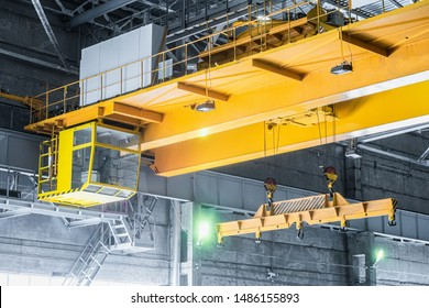Yellow overhead crane with linear traverse and hooks in engineering plant shop. Cabin of crane operator and jib crab trolley. Landing  staircase.