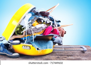 Yellow Overloaded Trunk Different Things Accessories Clothes Sunglasses Towels Passport Bikini Tickets Coat Hanger Concept Summer Holiday Travel Preparation Trip Background Isolated Blue