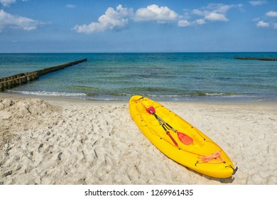 yellow paddle boat at a sandy  beach of the baltic sea with rows of groynes, concept for north european summer vacvation and sports, Gemany, Europe