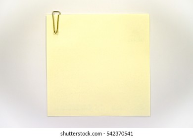 Yellow page and clip on white paper background