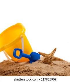 A yellow pail and blue shovel on a sandy beach with a starfish