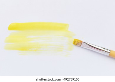 Yellow paint brush color on white paper background.