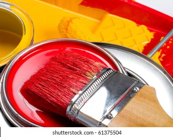 Yellow paint can and brush and roller