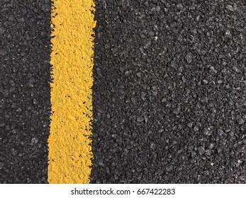 Yellow paint line on black asphalt road surface texture. space transportation background
