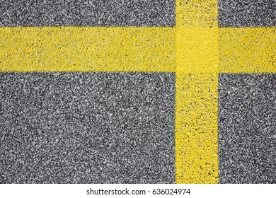 Yellow paint lines cross shape on black asphalt.