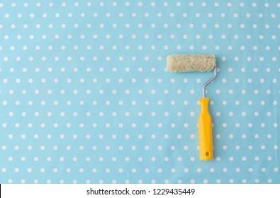 yellow paint roller over blue polka dot wallpaper in nursery room