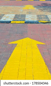 Yellow painted arrow sign on the brick pavement showing direction