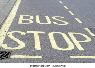 Yellow painted bus stop sign on a street