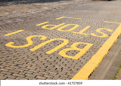 yellow painted BUS STOP sign on a paved street