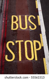 Yellow painted bus stop sign on a street. London