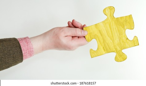 yellow painted puzzle piece in male hand on grey background