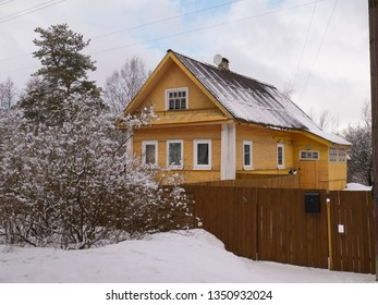 Yellow painted Russian izba rural house at winter season