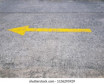 Yellow Painted Traffic Arrow Sign on Street Pointing to the Left