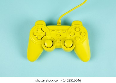 a yellow painted video game controller on a plain turquoise background. Minimal color still life photography
