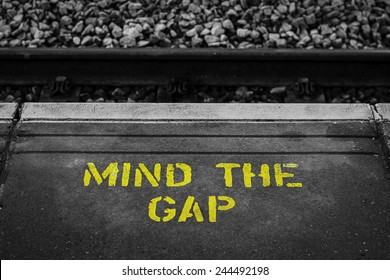 """A yellow painted warning sign """"Mind The Gap"""" at a British railway station"""