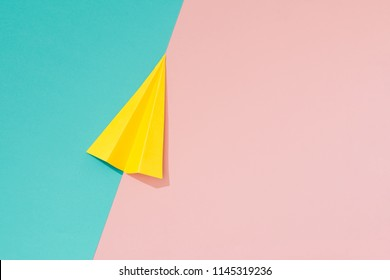 Yellow paper airplane on pastel pink and blue background. Minimal flat lay school concept.