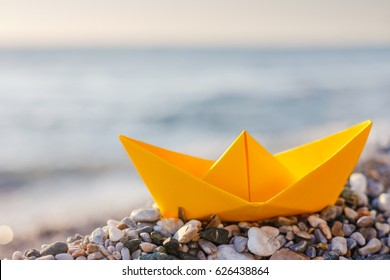 Yellow paper boat on the beach