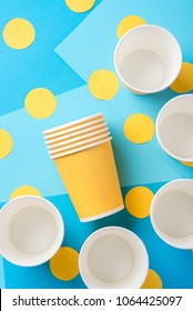 Yellow paper cups for a party on a bright blue background
