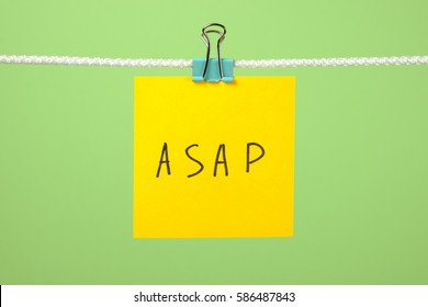 Yellow paper note on the string with text ASAP over colorful background