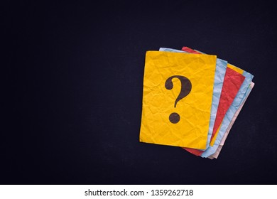 Yellow paper note with question mark on black board. Close up.