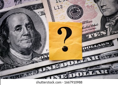 Yellow paper note with question mark on US dollar background. Close up.