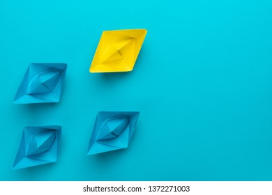 yellow paper ship ahead of blue ones leadership concept over blue background. top view of race with yellow winning paper ship metaphor. minimalist conceptual image of leadership with copy space