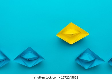 yellow paper ship out of the crowd concept over blue background. top view of race with yellow paper ship leaving the crowd metaphor