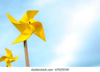 Yellow paper windmills, with blue sky background.