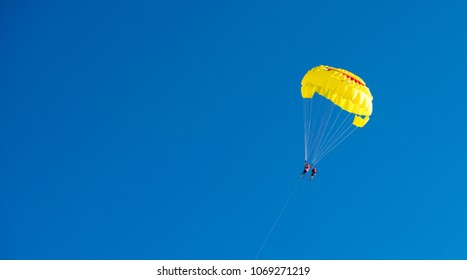 yellow parachute flight. A parachute with a smile. Rest on the water. Journey through the sky. Active time at the resort. Beach entertainment.